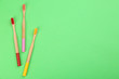 canvas print picture - Natural toothbrushes made with bamboo on green background, flat lay. Space for text