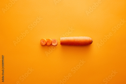 Cuadros en Lienzo Top view of carrot with slices on orange background