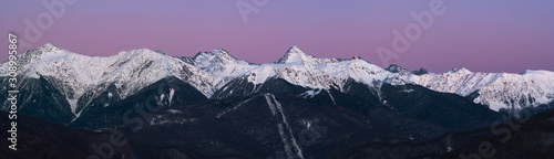 Panorama of snowy mountains ridge at pink and blue sky background at sunset Wallpaper Mural