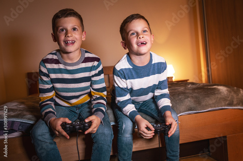 Fototapeta Two little brothers sitting at home on pleasant evening and playing games on console