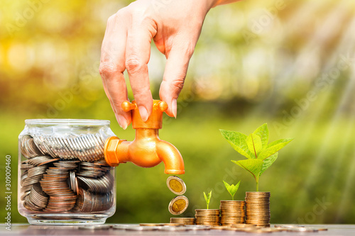 Fotomural Woman's hand open a faucet of jar and gold coin drop for invest with growing money and seed put on the wood in the public park, for currency and financial business investment and fund concept