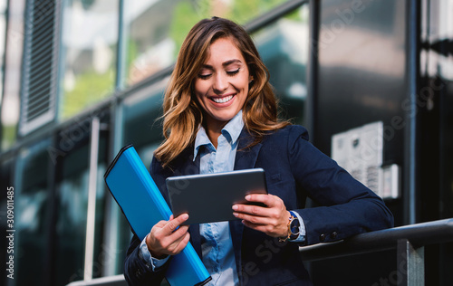 Obraz Young businesswoman working with tablet outdoor. Business, education, lifestyle concept - fototapety do salonu