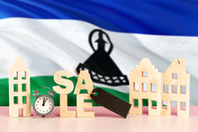 Lesotho Real Estate Sale Concept. Wooden House Model With Discount Tag On National Flag Background. Copy Space For Text.