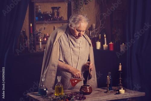 Fotografie, Obraz elderly alchemist monk brews  magic potion