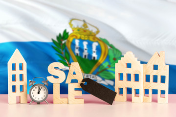 San Marino real estate sale concept. Wooden house model with discount tag on national flag background. Copy space for text.