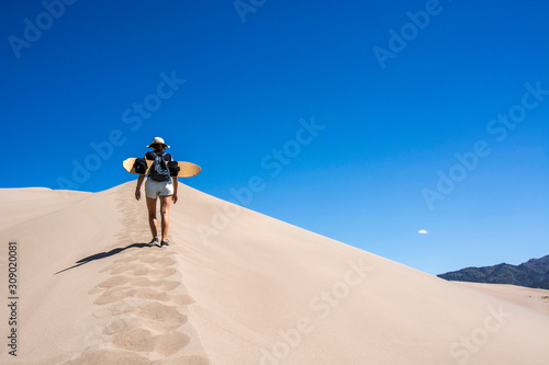 woman with sand board walking on edge of a sand dune in the great sand dunes nat Fototapete
