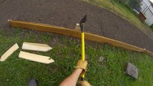 Home Gardening - Slow Motion Of Man Using Hatchet Back Side To Strike And Secure Wooden Post To Support Small Short Fence Or Garden Bed Border. View From First Person Perspective, Wide Angle Lens