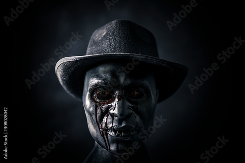 Photo Scary figure with creepy bloody mask and hat in the dark