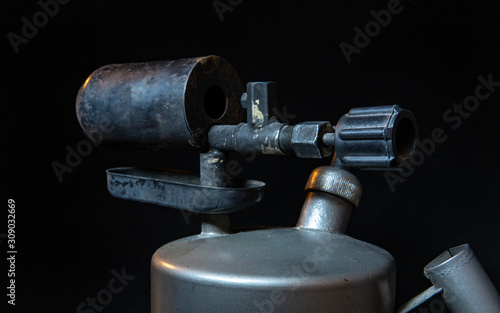 old blowtorch on a black background Wallpaper Mural