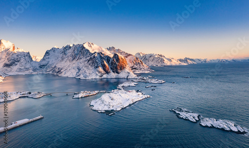 Amazing aerial view of Lofoten Islands nature from drone, winter sunrise snowy scenery of village Reine, Sakrisoy and Hamnoy during beautiful mountain ridge with alpenglow, scene over polar circle Wallpaper Mural
