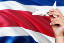 Costa Rica Travel Concept. Woman Holding A Miniature Plane On National Flag Background. Holiday And Voyage Theme With Copy Space For Text.