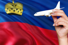 Liechtenstein Travel Concept. Woman Holding A Miniature Plane On National Flag Background. Holiday And Voyage Theme With Copy Space For Text.