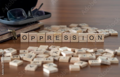 Fotografie, Tablou  oppression the word or concept represented by wooden letter tiles