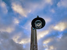 Low Angle Of A Lamp Post At The Boat Docks On Lake Washington, Against A Cloudy Blue Sky