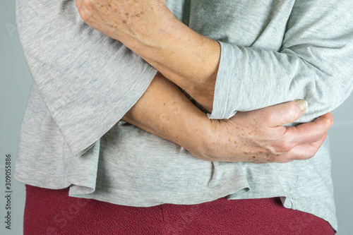 caucasian elderly woman with her hand on her elbow, isolated on White background Canvas Print