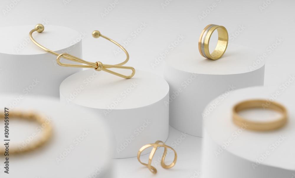 Fototapeta Modern Golden bow shape bracelet and rings collection on white cylinders platform