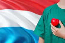 Luxembourg Veterinary Clinic Concept. Veterinarian Is Holding Plastic Heart In Green Uniform On National Flag Background. Animial Love Theme.