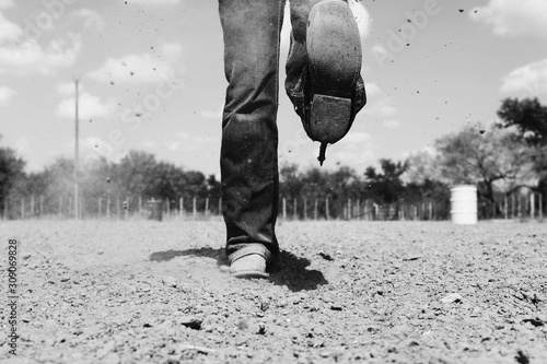 Obraz na plátne Cowgirl woman with cowboy boots and spurs in outdoor dirt arena, western lifestyle concept in black and white