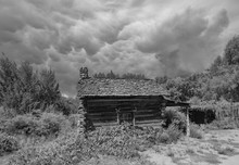 An Old Log Cabin With Storm Cl...