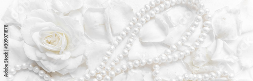 Foto Beautiful white rose and pearl necklace on a background of petals