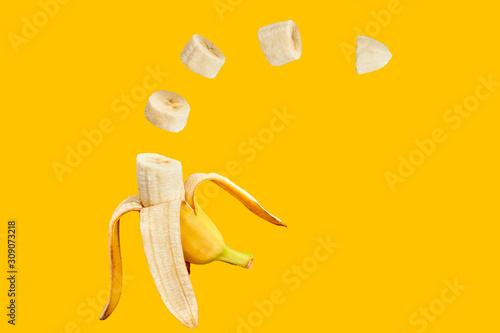 Fototapeta Banana open and sliced with orange background obraz