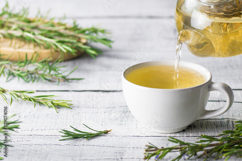 White cup of healthy rosemary tea pouring from teapot with fresh rosemary bunch Fototapeta