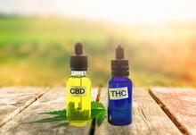 THC And CBD Oil Bottles On Woo...