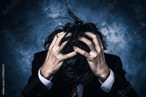 Photo 頭を抱えるビジネスマン