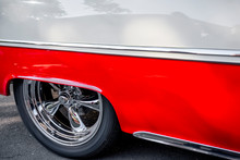 Rear Wheel With Chrome Rim Under A Low Quarter Of A Red And White Vintage Retro Car