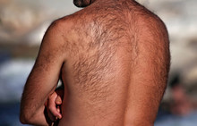 Man With A Very Hairy Back Standing Outside By A River On A Hot Summer Day