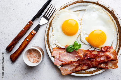 Obraz Fried eggs and bacon for breakfast on a plate, top view, copyspace - fototapety do salonu