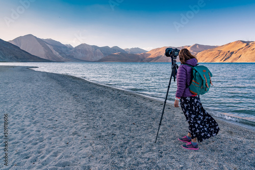 Backpack photographer woman taking a photo with DSLR camera on tripod with beautiful landscape with mountain at Pangong lake, Leh , India Canvas Print