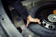 Close Up Mechanic Hand Taking Spare Tire At Boot