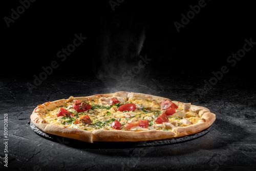 Hot tasty traditional italian pizza with salami, cheese, tomatoes greens on a dark background