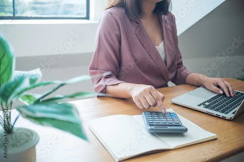 Fototapeta Business women checking  bills. taxes bank account balance and calculating  annual financial statements of company. Accounting  Audit Concept obraz