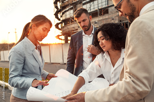 Business partners discussing a blueprint in front of the construction site.