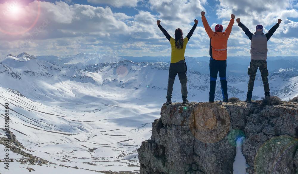 Fototapeta successful mountaineering team achieving the goal of winter climbing