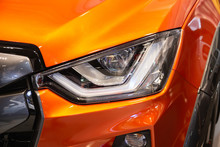 Close Up Of Detail On One Of The LED Headlights Modern And Luxury Orange Car. Select Focus.