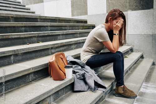 Canvastavla Pretty young woman sitting on steps outdoor and covering face when crying after