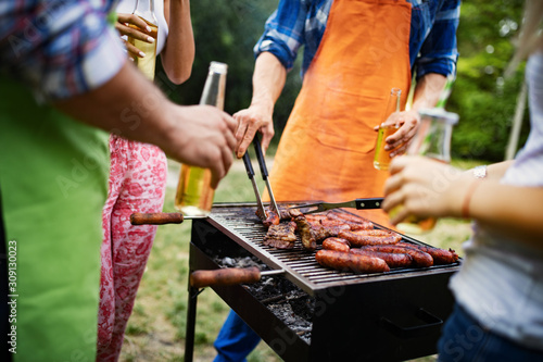 Canvas Print Group of friends camping and having a barbecue in nature