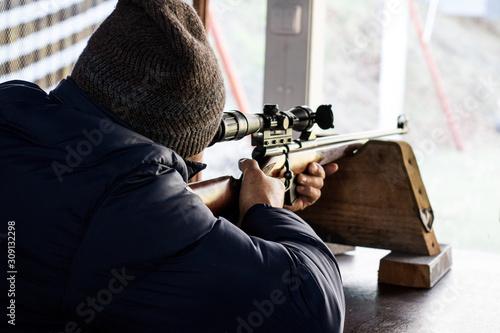 Fotografía man takes aim at a rifle at a shooting range