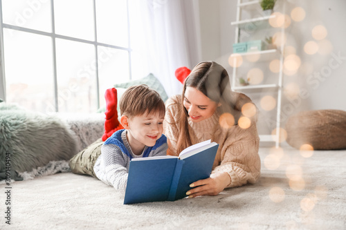 Cute little boy with mother reading book at home