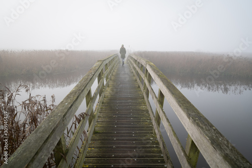 A woman walking on a small footbridge on a foggy day in autumn. Fototapet