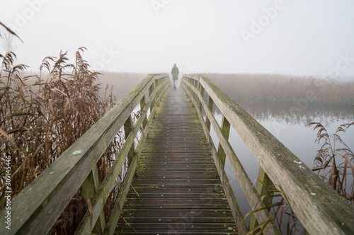 Canvas Print A woman walking on a small footbridge on a foggy day in autumn.