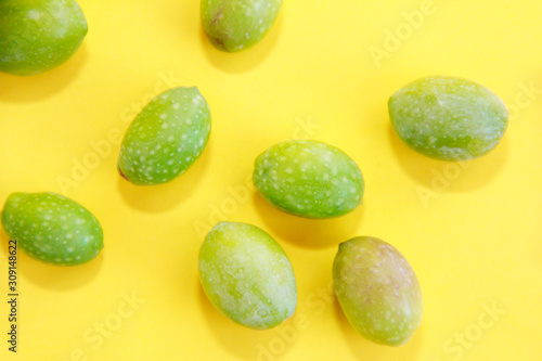 Fototapeta natural green fresh olives on a yellow background