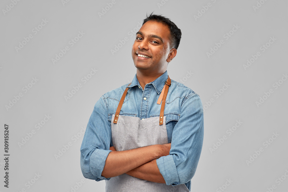 Fototapeta people, job and profession concept - smiling indian barman, waiter or salesman in apron over grey background