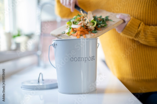 Obraz Close Up Of Woman Making Compost From Vegetable Leftovers In Kitchen - fototapety do salonu