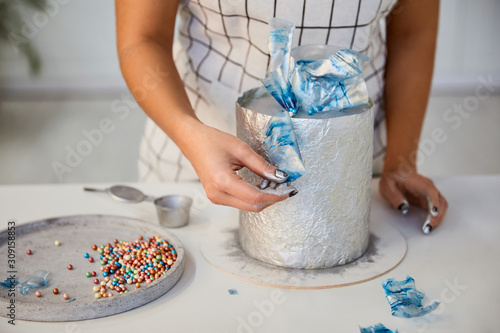 Fototapeta Partial view of confectioner decorating cake on table obraz