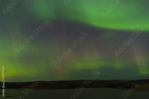 Vászonkép Northern lights over the lake and hills
