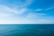 Leinwandbild Motiv cloudy blue sky leaving for horizon above a blue surface of the sea